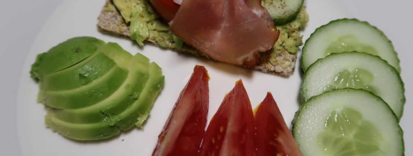 Knäckebrot mit Avocado, Tomaten, Gurken und Rohschinken